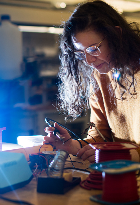 Female student working in mechanical lab with circuits