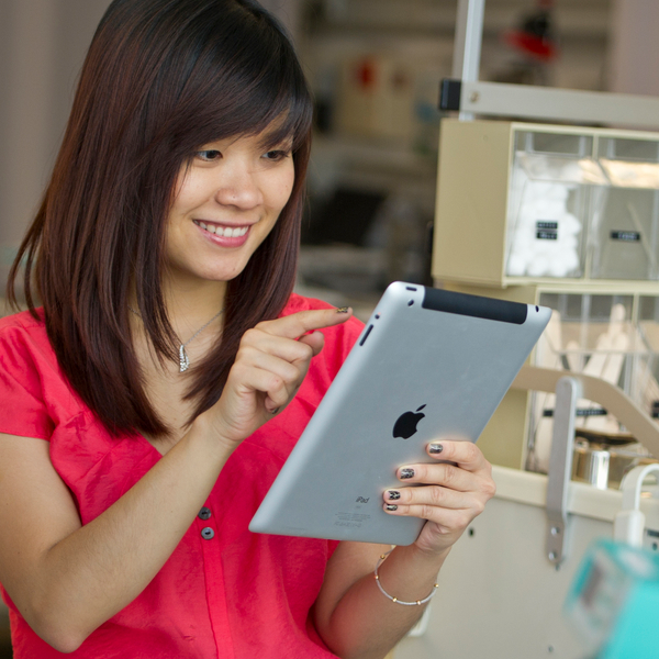 woman smiling about to touch an Apple ipad device in a lab