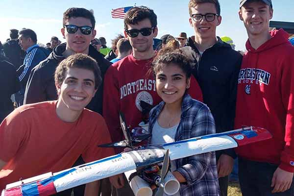 rocket club team poses holding rocket in a field