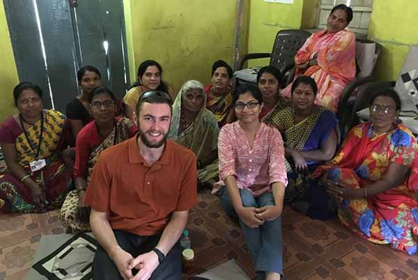 student sitting with group in India