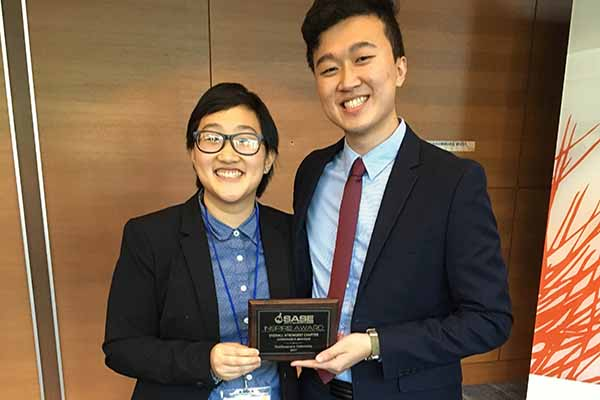 two Asian students with award plaque in hands smiling