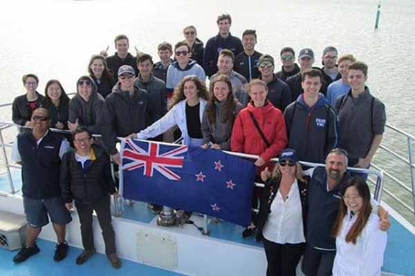 group of dozen-plus students at helm of boat holding New Zealand flag