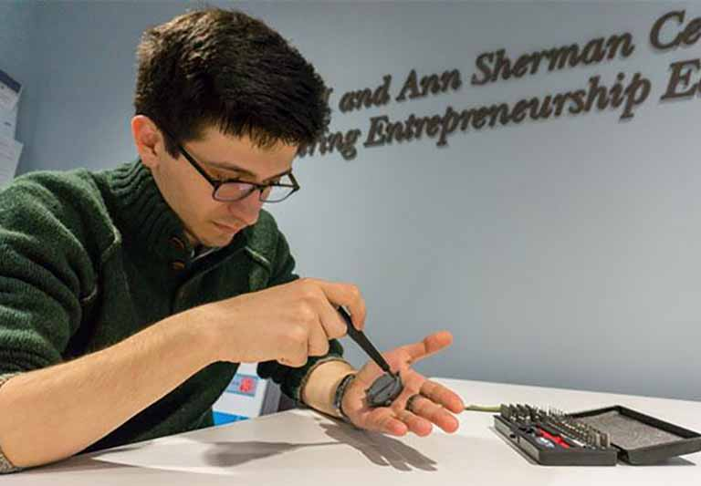 student with glasses looking down while holding component of a watch screwing a piece in his palm