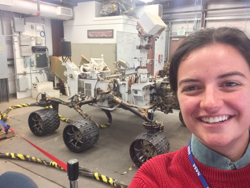 student with NASA landyard poses for selfie with NASA rover in the background
