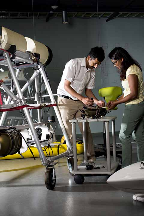 student and professor working with wires on robots on table