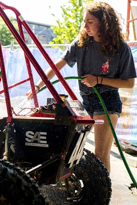 student with hose spraying water to wash the Baja vehicle outside on sunny day