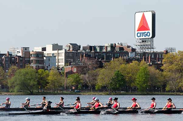 rowing team on the Charles River rowing in a canoe with city buildings and the Citgo sign in the background