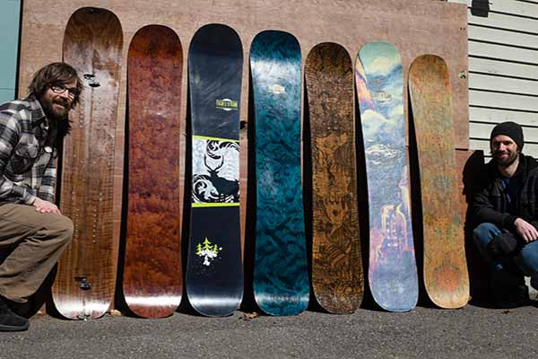 skateboards lined up along wall with two founders on each end